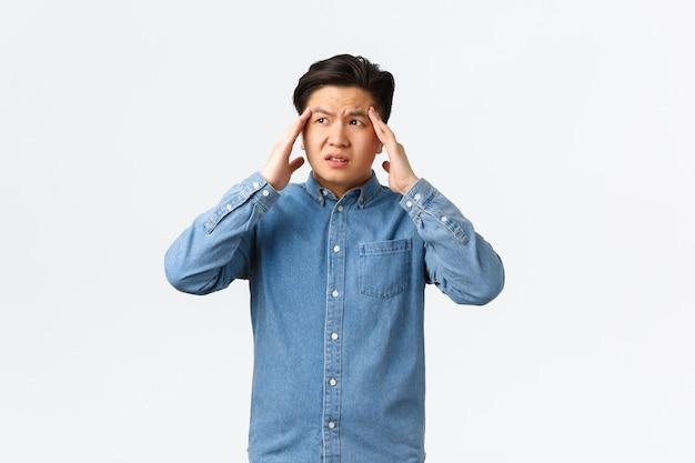 Homme asiatique troublé et mal à l'aise ayant l'air perplexe, ayant une situation compliquée. guy avec des maux de tête touchant la tête et détournant les yeux, souffrant de migraine douloureuse, debout sur fond blanc