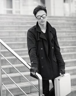 Homme asiatique avec une valise en métal dans la ville. boitier asiatique et argent. asiatique avec une valise pour tueur. détective avec les marchandises dans l'affaire.