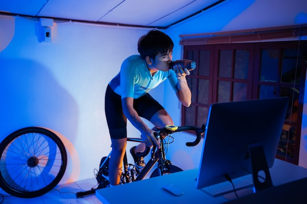 Homme asiatique à vélo sur l'entraîneur de machine qu'il exerce à la maison la nuit.