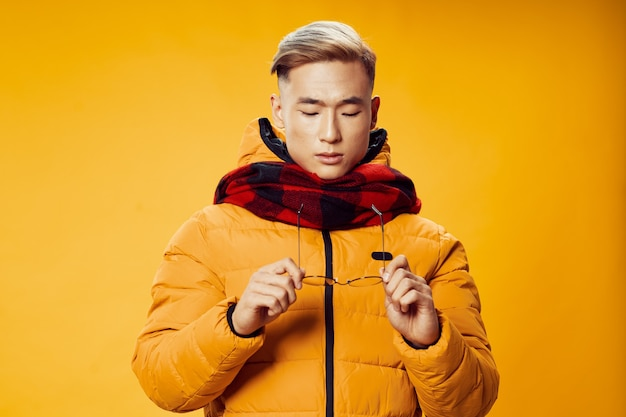 Homme asiatique en vêtements d'hiver et écharpe à carreaux