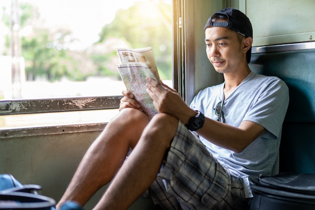 Homme asiatique voyageant carte de lecture routard assis sur le vieux siège de train en thaïlande