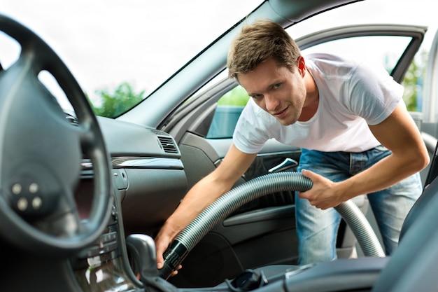 L'homme aspire ou nettoie la voiture