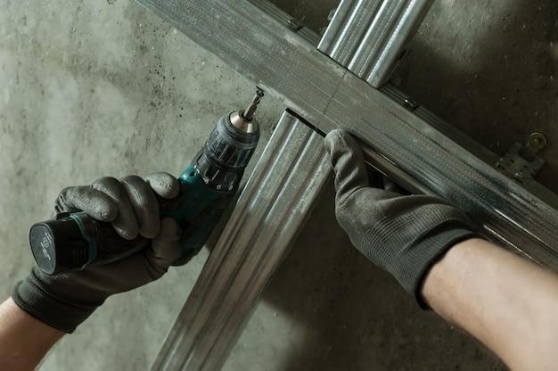 L'homme assemble le cadre en métal de profil