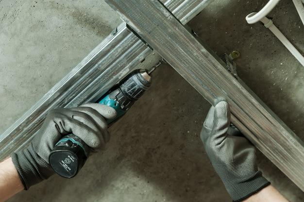L'homme assemble un cadre métallique profilé pour plafonds en plaques de plâtre