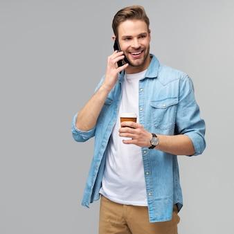 Homme assez décontracté en chemise de jeans bleu tenant son téléphone et une tasse de café à emporter
