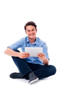 Homme assis à l'aide d'une tablette numérique