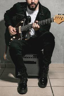Homme assis sur un amplificateur et jouant de la guitare