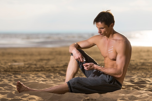 Homme assis et application de lotion solaire