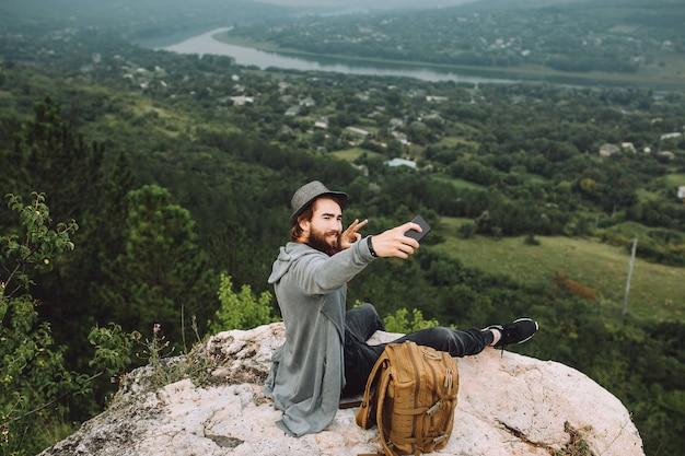 Homme assis au sommet de la montagne prendre selfie