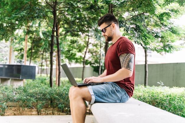 Homme assis sur un banc au milieu d'un parc travaillant à distance avec son ordinateur portable