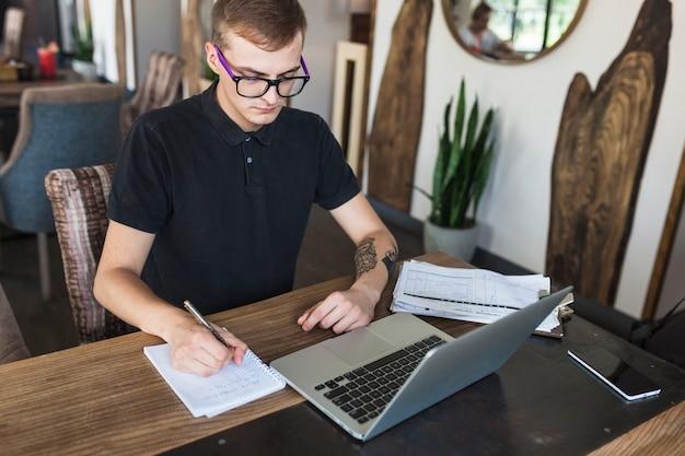 Homme assis avec bloc-notes et ordinateur portable à la table