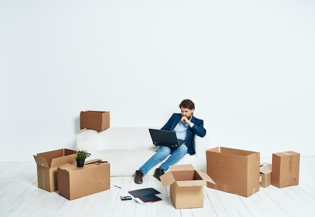 Homme assis sur des boîtes de canapé avec des choses nouveau lieu de travail professionnel de bureau.