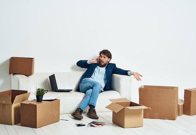Un homme assis sur le canapé à parler au téléphone une boîte officielle de choses