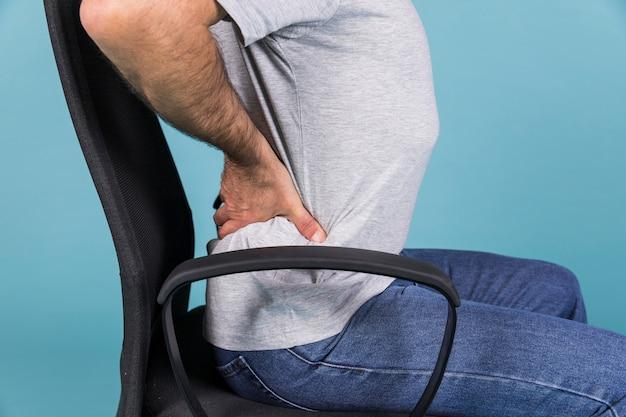 Homme assis sur une chaise, avoir mal au dos sur fond bleu