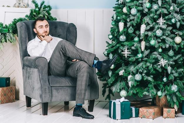 Un homme assis sur une chaise près de l'arbre de noël