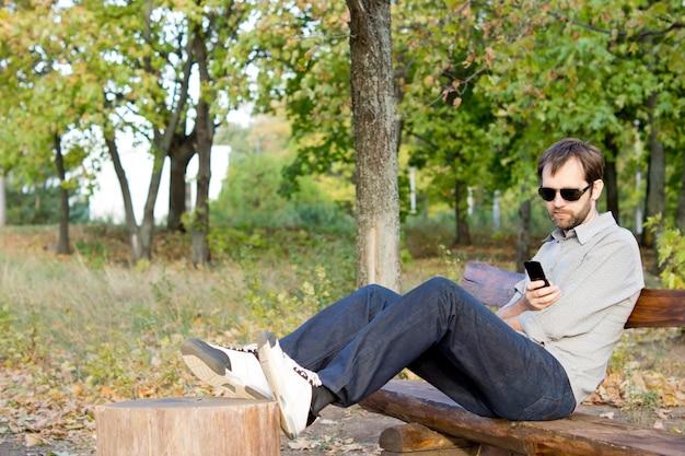 Homme assis confortablement sur un banc de parc en bois avec ses pieds en lisant un message sur son téléphone mobile