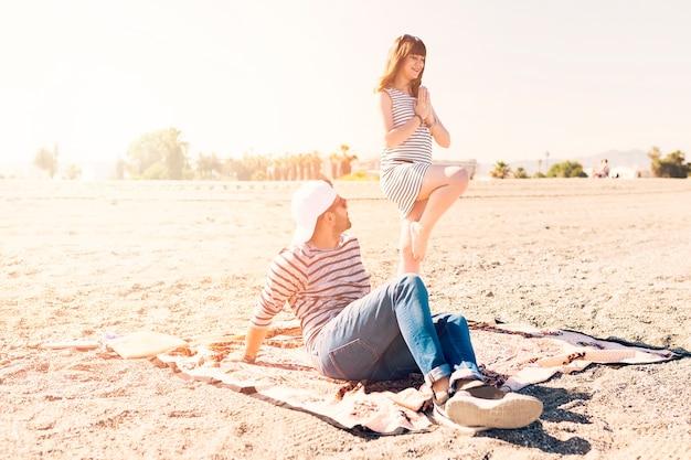 Homme assis sur une couverture à la recherche de sa copine, faire du yoga à la plage