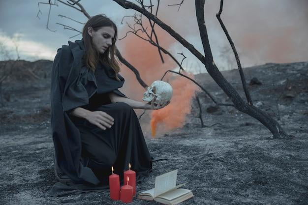 Homme assis avec un crâne dans la main et en regardant