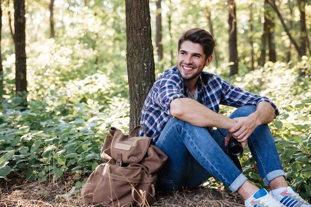 Homme assis dans la forêt près du sac à dos