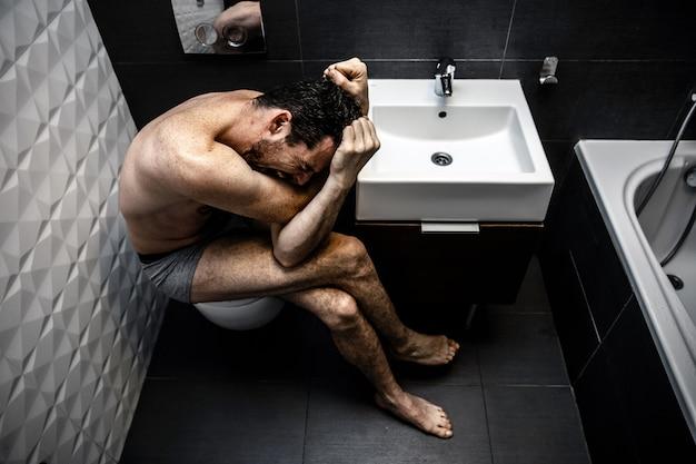 Homme assis dans la salle de bain