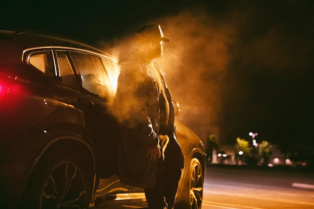 Homme assis dans la voiture la nuit