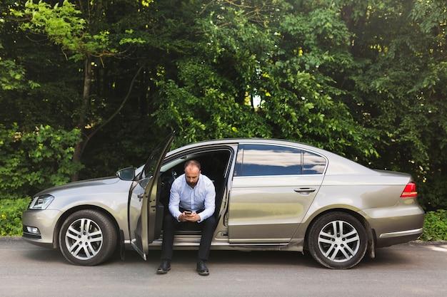 Homme assis dans une voiture avec porte ouverte à l'aide d'un téléphone mobile