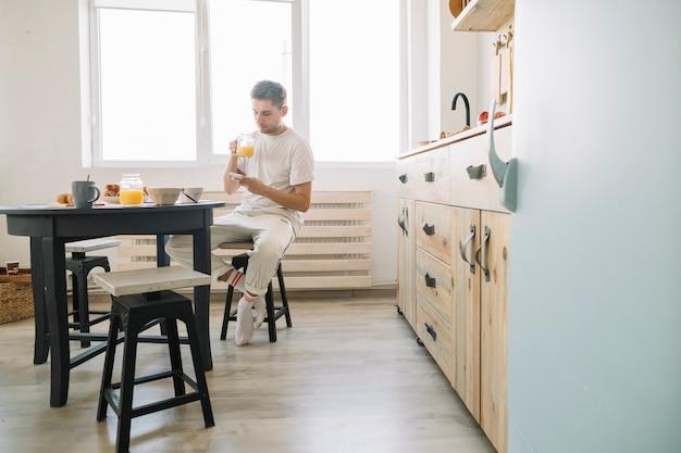Homme assis devant une table à manger ayant du jus avec un téléphone portable