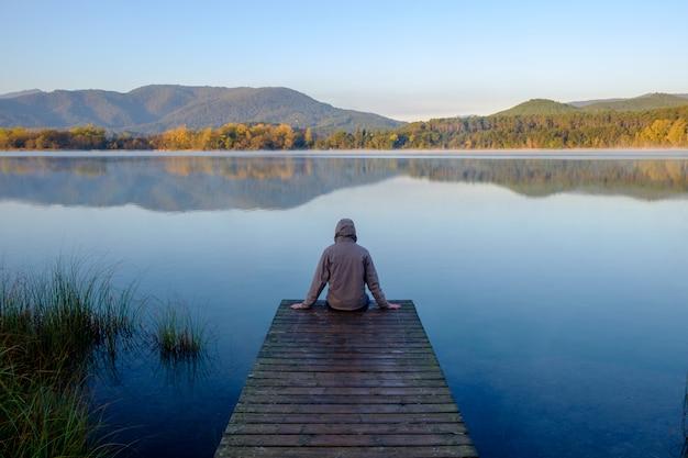 Homme assis sur le dos sur une jetée