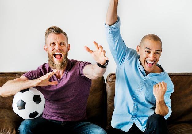 Homme assis ensemble sur un canapé en regardant le sport