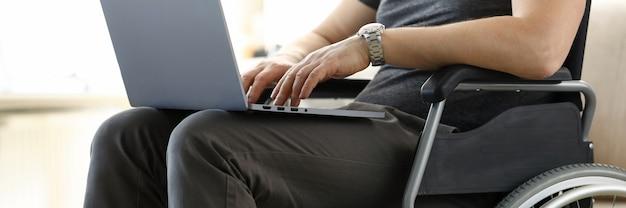 Homme assis en fauteuil roulant travaillant avec le concept d'ordinateur portable