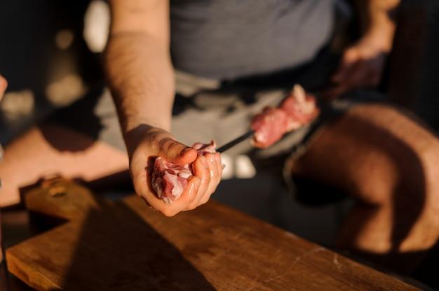 Homme assis ficelant des morceaux de viande fraîche sur des brochettes en acier