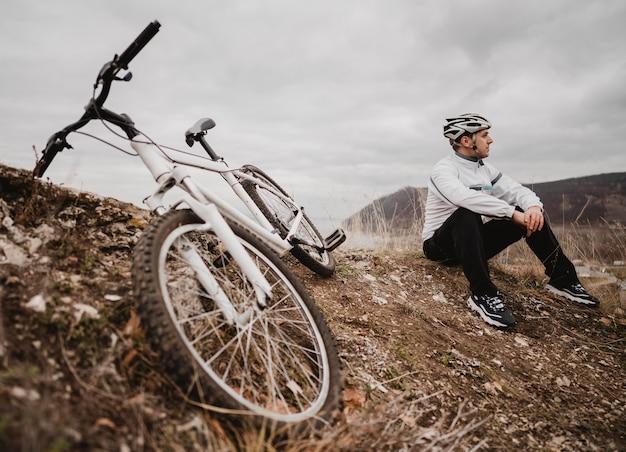 Homme assis sur l'herbe à côté de son vélo de montagne