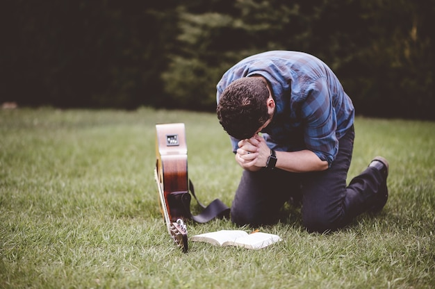 Homme assis sur l'herbe et priant avec un livre et une guitare près de lui