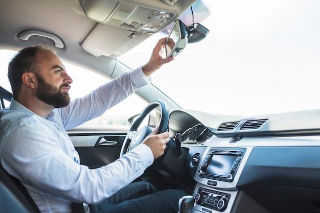 Homme assis à l'intérieur de la voiture en ajustant le rétroviseur