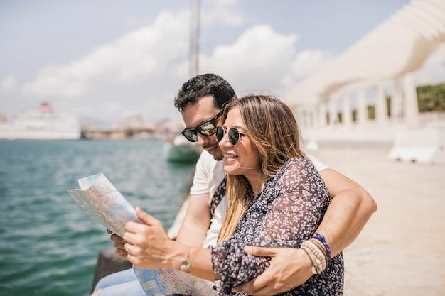 Homme assis sur la jetée étreignant sa copine en quête de direction sur la carte
