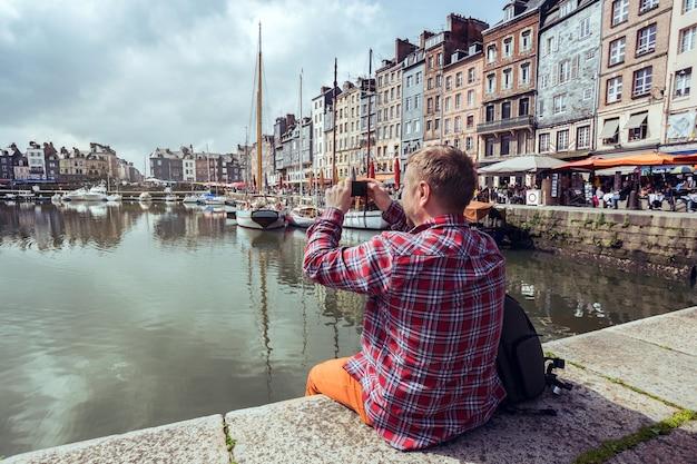 Homme assis sur une jetée et prenant une photo du port de honfleur avec son smartphone