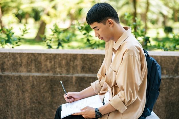 Un homme assis et lisant un livre dans les escaliers.