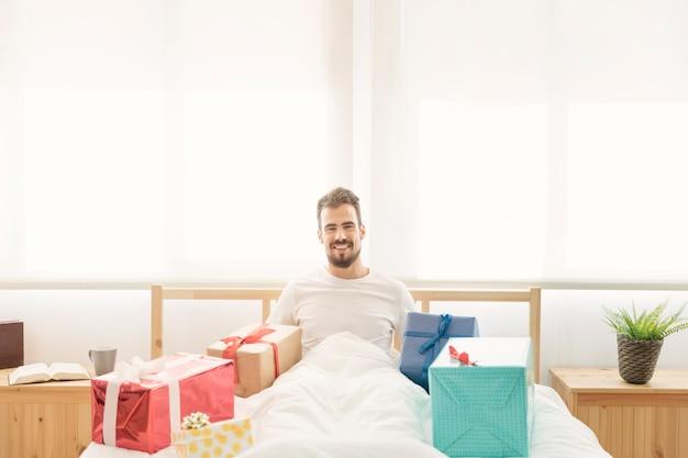 Homme assis sur le lit avec des cadeaux colorés
