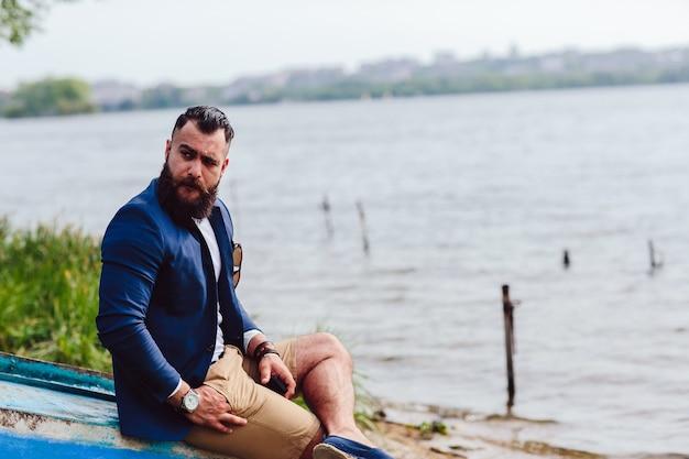 L'homme assis avec une main dans sa poche en plein air