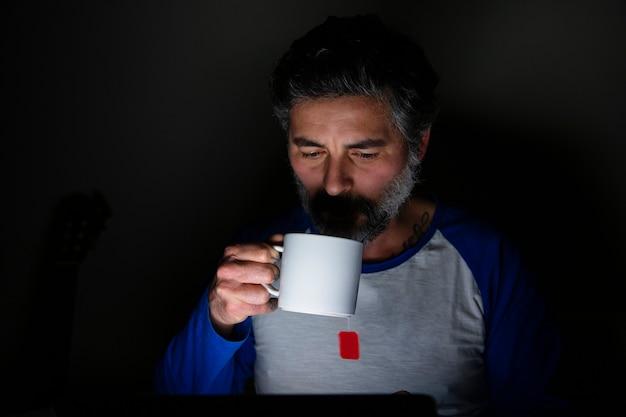 Homme assis à la maison avec une tasse de thé la nuit avec un ordinateur portable.