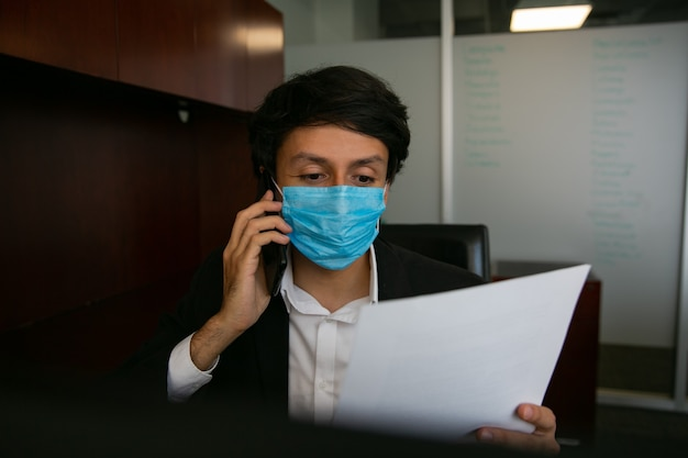 Un homme assis à parler au téléphone, il porte un masque de protection pour la prévention des virus