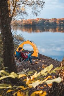 Homme assis sur la plage du lac près de la tente à la recherche de téléphone. saison de l'automne.