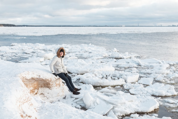 Homme assis sur une plage glacée le long de la mer