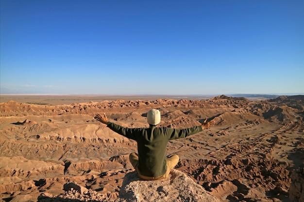 Homme assis sur le rocher appréciant la vue imprenable sur la vallée de la lune, désert d'atacama, chili