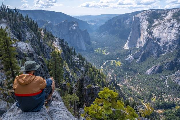 Homme assis sur un rocher dans le parc national de yosemite, sentinel dome yosemite usa