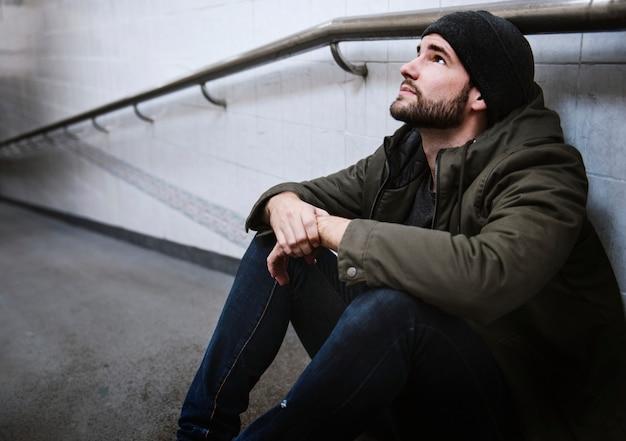 Homme assis sans espoir sur le sol