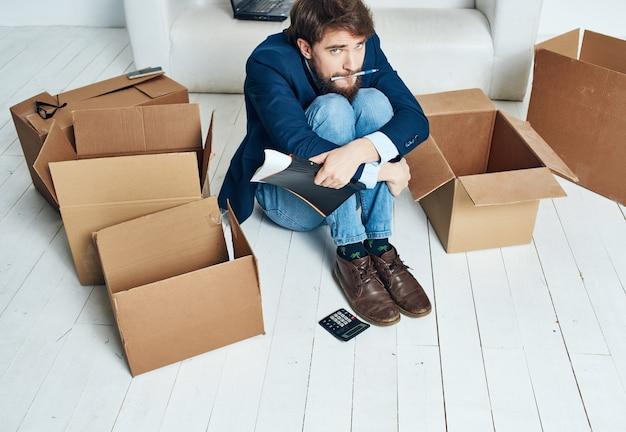 Homme assis sur le sol des boîtes avec des choses bureau nouveau lieu de travail mode de vie