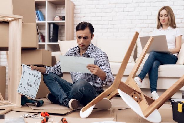 Homme assis sur le sol, lecture des instructions de meubles.