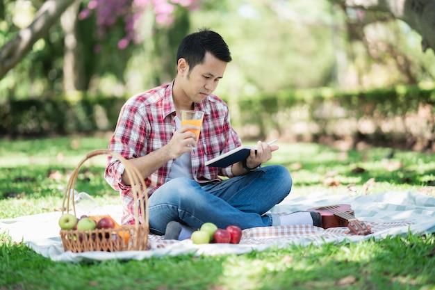 Homme assis sur le sol et livre de lecture