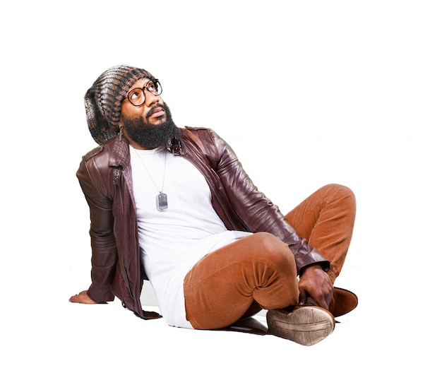 L'homme assis sur le sol avec les pieds joints